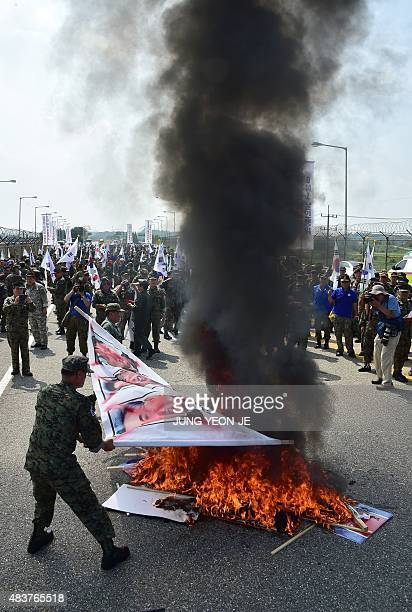South Korean veterans set fire to a banner showing portraits of North Korean leaders during a protest in Paju on August 13 denouncing a recent...