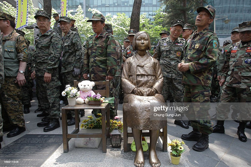 South Korean Vietnam War veterans stand beside a comfort women statue during their rally in front of Japanese embassy on May 23, 2013 in Seoul, South Korea. Recent remarks by the mayor of Osaka on the historic perception of 'comfort women', conscripted by Japanese military brothels during World War II, have recieved intense criticism from neigbouring countries and the US.