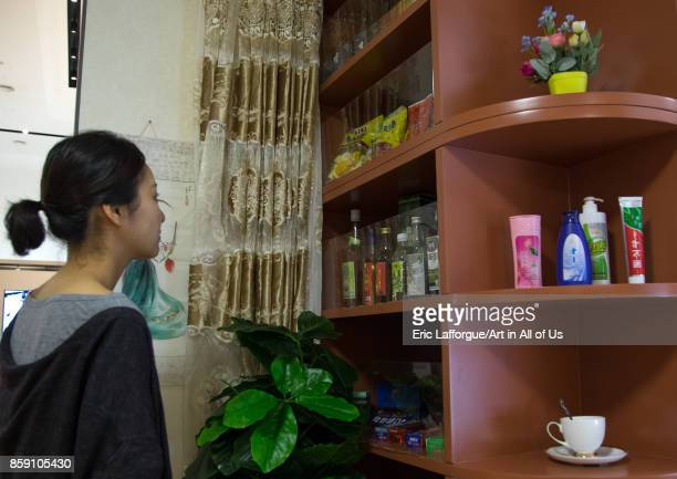 South Korean visitor looking at bottles during the exhibition Pyongyang sallim at architecture biennale showing a north Korean apartment replica...