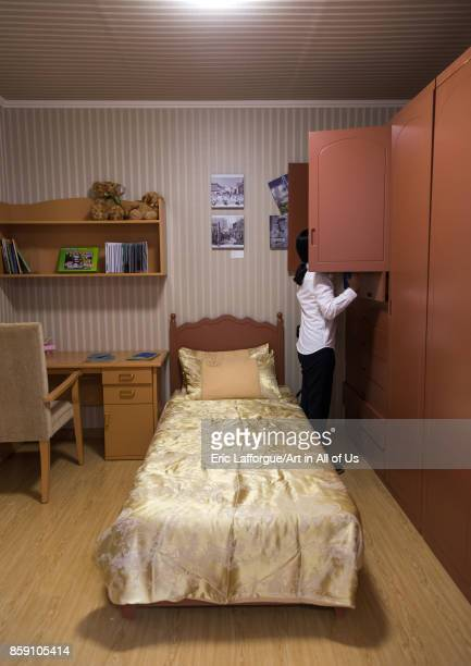 South Korean visitor looking in a cupboard of a bedroom during the exhibition Pyongyang sallim at architecture biennale showing a north Korean...