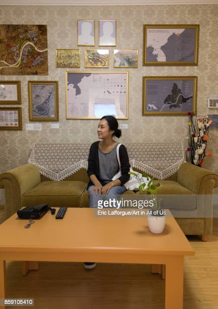 South Korean visitor sit below the portraits of the dear leaders with the pictures removed during the exhibition Pyongyang sallim showing a north...