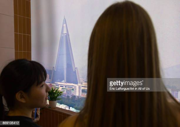 South Korean visitors looking thru a fake balcony during the exhibition Pyongyang sallim at architecture biennale showing a north Korean apartment...