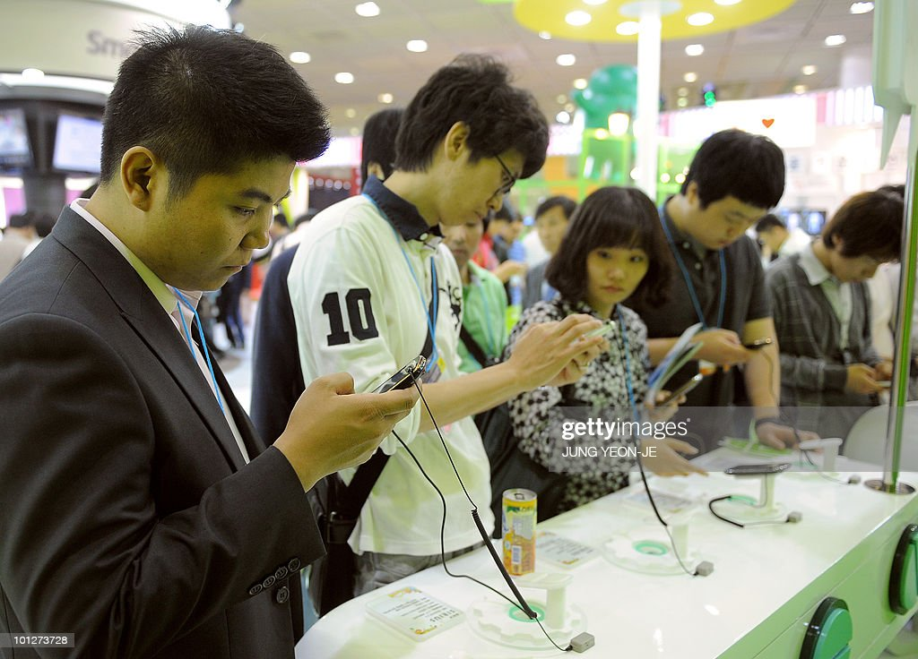 South Korean visitors touch smart phones during the World IT Show in Seoul on May 28, 2010.
