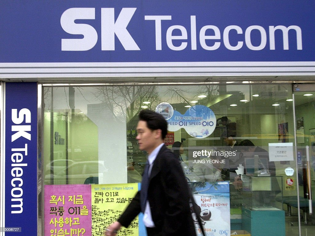 A South Korean walks past a SK Telecom shop in Seoul, 24 February 2004. SK Telecom, South Korea's biggest mobile phone operator, said it had agreed with French telecom equipment giant Alcatel to jointly develop and sell multimedia messaging services worldwide. A memorandum of understanding was signed in November and a contract will be inked in March, a spokesman of SK Telecom said.