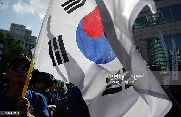 South Korean war veterans hold national flags aloft during a protest as South Korea marks the 68th Independence Day on August 15 2013 in Seoul South...