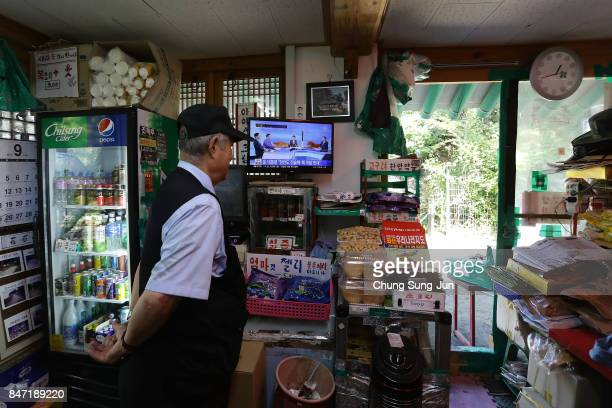 South Korean watches a television broadcast reporting the North Korean missile launch at the their store near the demilitarized zone of Panmunjom on...
