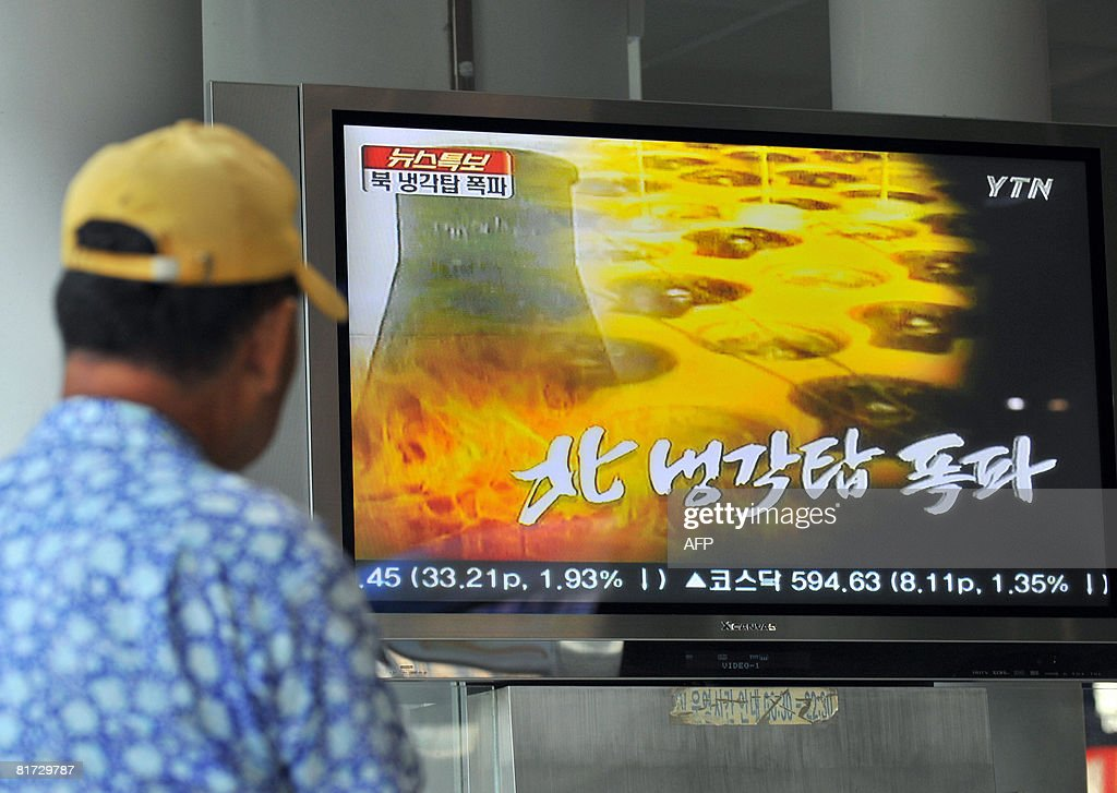 A South Korean watches a TV news programme at a railway station in Seoul on June 27 2008 about the planned blowup of a cooling nuclear tower at North...