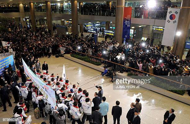 South Korean Winter Olympic athletes wave to fans and ranks of press upon their arrival at Incheon international airport west of Seoul on March 2...