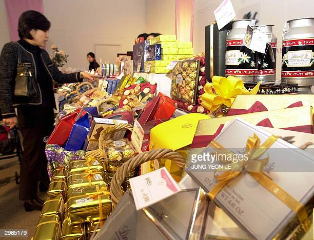 South Korean woman buys boxes of chocolates as a gift for Valentine's Day at a department store in Seoul 11 February 2004 South Korean women feel the...