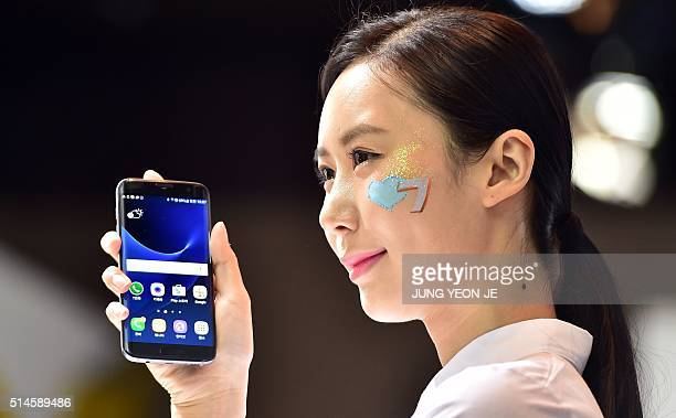 A South Korean woman holds up Samsung Electronics' latest flagship smartphone the Galaxy S7 edge during a showcase to mark the domestic launch in...