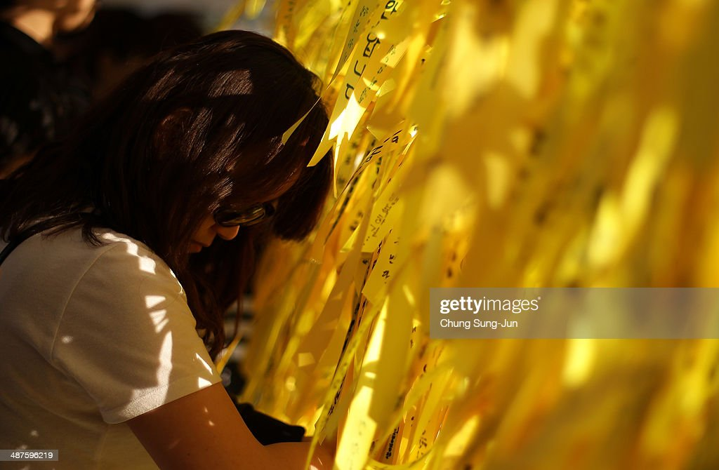 A South Korean woman ties a yellow ribbon of hope for the safe return of missing passengers of sunken ferry Sewol at a group memorial altar on May 1, 2014 in Seoul, South Korea. No survivors have been found since 174 passengers and crew were rescued on the day of the incident, April 16.