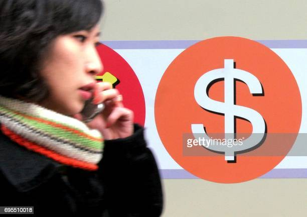 A South Korean woman walks past a sign of a foreign exchange bank in Seoul 23 February 2005 South Korea's central bank denied it planned to shed its...