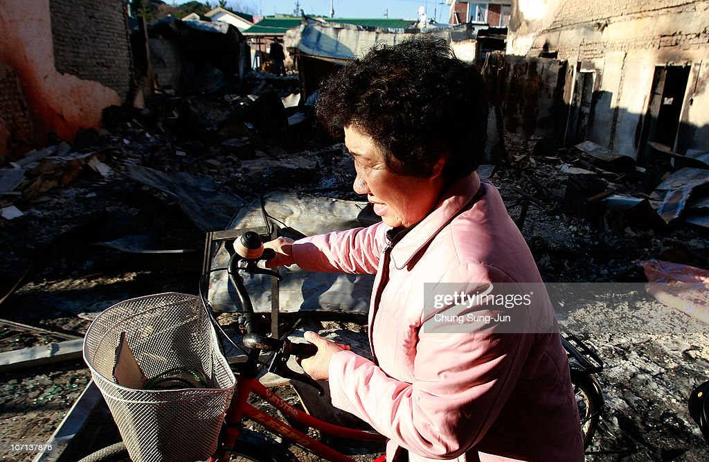 South Korean woman who will be evacuated from Yeonpyeong island walks her bicycle past destroyed houses on November 25 2010 in Yeonpyeong Island...