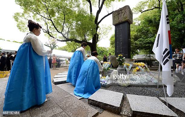 South Korean women clad in traditional costumes offer flowers and prayers for the Korean victims of the 1945 atomic bombing before a monument at the...