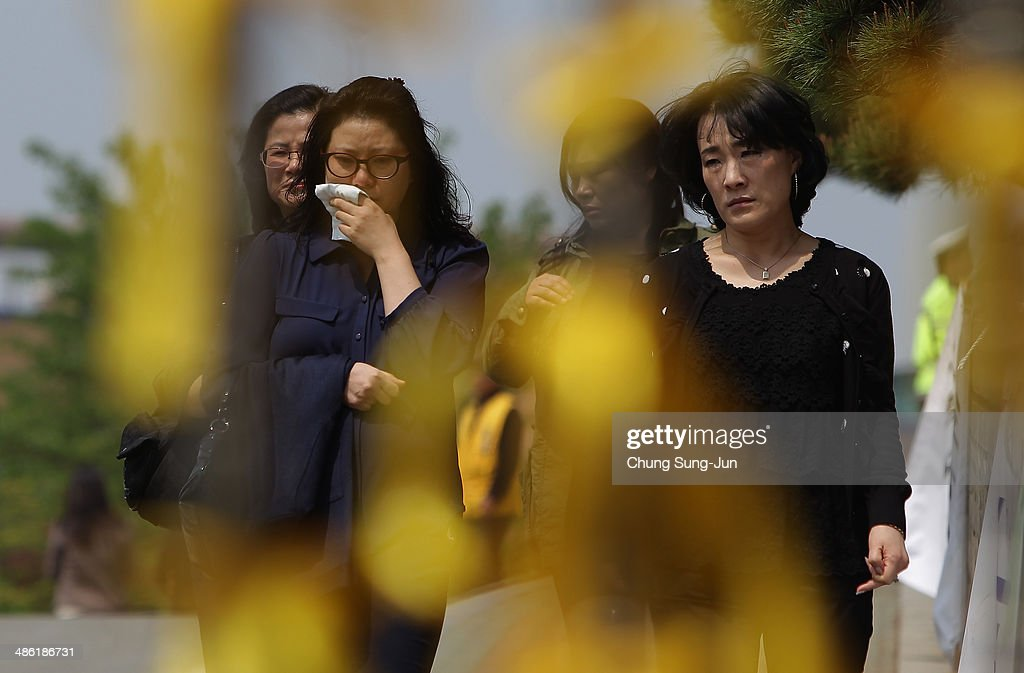 South Korean women weep after visit Danwon high school on April 23, 2014 in Ansan, South Korea. At the altar, Friends and relatives are able to pay tribute to those who have passed in the April 16 ferry disaster off of Jindo Island in South Korea. The confirmed death toll now reached 150, and more than 150 people are still missing, as reported.
