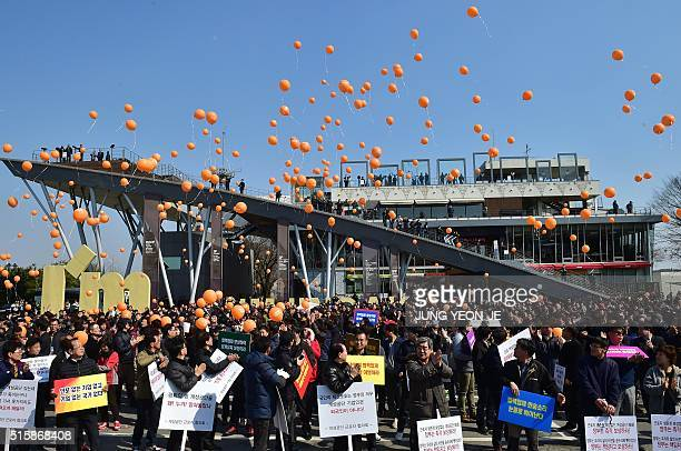 South Korean workers release orange balloons reading 'substantial compensation and reopen of the industrial complex' during a rally against the...