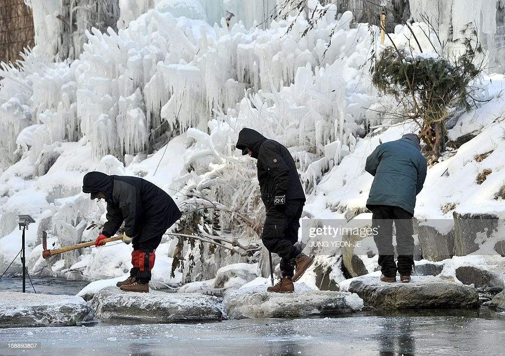 South Korean workers smash ice on stepping stones at the Cheonggye stream in central Seoul on January 3, 2013. South Korea's electricity consumption shot up to a new all-time high on January 3, as temperatures dropped to this winter's lowest of 16.4 degrees Celsius (3 F) below zero in Seoul.