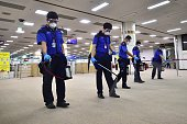 South Korean workers spray antiseptic solution at the customs immigration and quarantine office of Gimpo international airport in Seoul on June 17...