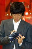 South Korean World Cup star Park JiSung signs a soccer shoe during the opening ceremony of his memorial hall in a World Cup Stadium in Suwon south of...