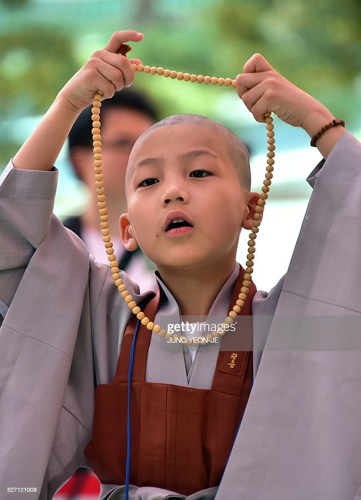 A South Korean young novice monk holds his new prayer beads after having his head shaved during a ceremony entitled 'Children Becoming Buddhist Monks', at the Jogye temple in Seoul on May 2, 2016. Following the ceremony the children stay at the temple where they are taught about Buddhism, for two weeks, until Buddha's birthday on May 14. / AFP / JUNG
