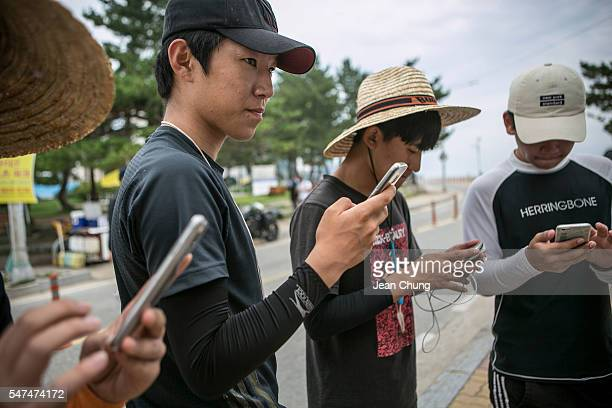 South Korean youths play Pokemon Go on July 15 2016 in Sokcho South Korea South Korea is not one of the initial Pokemon Go released countries nor is...