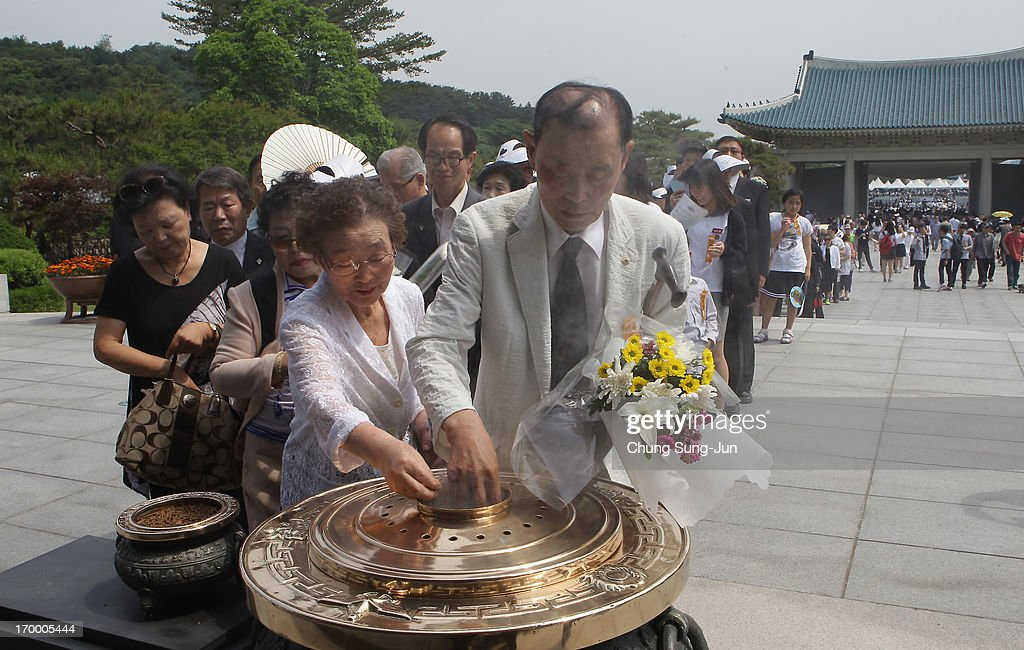 South Koreans burn incense during a ceremony marking Korean Memorial Day at the Seoul National Cemetery on June 6, 2013 in Seoul, South Korea. South Korea today marks the 58th anniversary of the Memorial Day for those killed in the 1950-53 Korean War.