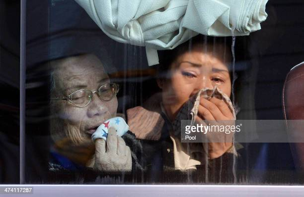 South Koreans in a bus bid farewell to their North Korean relatives before they return to their home after a family reunion having been separated for...