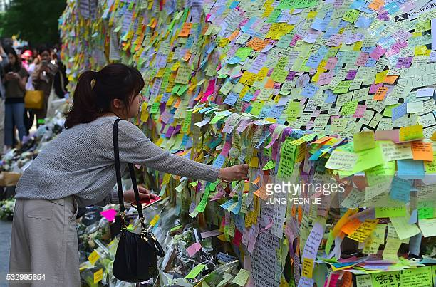 South Koreans leave messages written on postit notes at an exit of Gangnam subway station which has been turned into a mini shrine for a 23yearold...