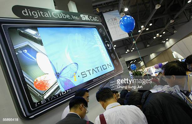 South Koreans look at mobile phones on display in the Korea Electronics Show 2005 on October 11 2005 in Goyang South Korea's Ministry of Information...
