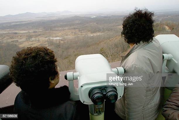 South Koreans look in the direction of North Korea near the demilitarized zone at the Dora Observation Post on February 15 2005 in Paju South Korea...