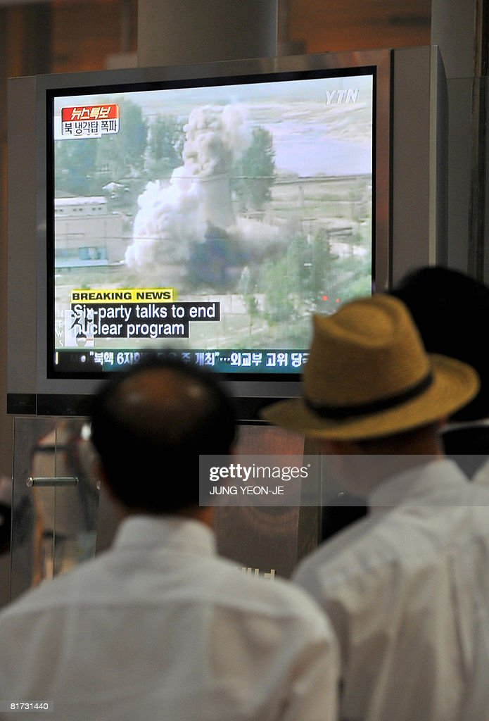 South Koreans looks at a TV screen reporting the public demolition of North Korea's cooling tower at its Yongbyon nuclear complex at a railway...
