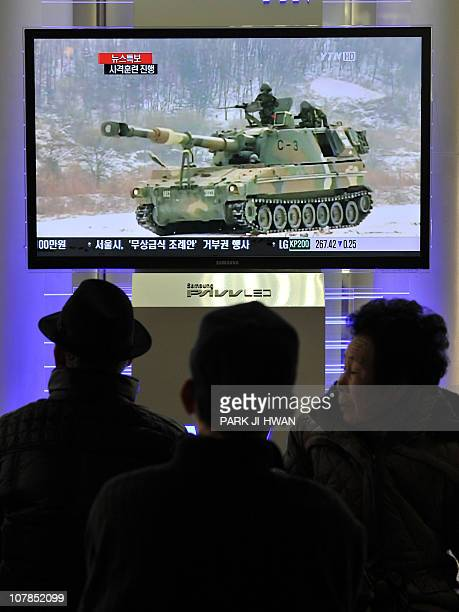 South Koreans watch a live TV breaking news about South Korea's live fire artillery at Seoul train station in Seoul on December 20 2010 South Korea...