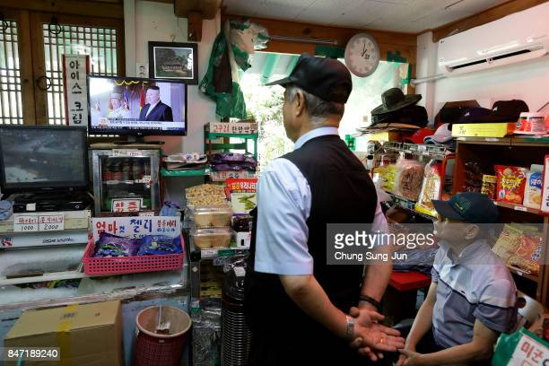 South Koreans watch a television broadcast reporting the North Korean missile launch at the their store near the demilitarized zone of Panmunjom on...