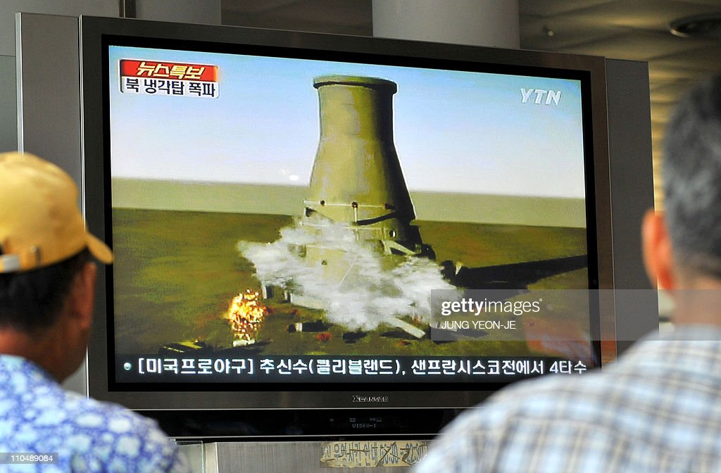 South Koreans watch a TV news programme at a railway station in Seoul on June 27 2008 that shows a mock video of the planned blowup of a cooling...