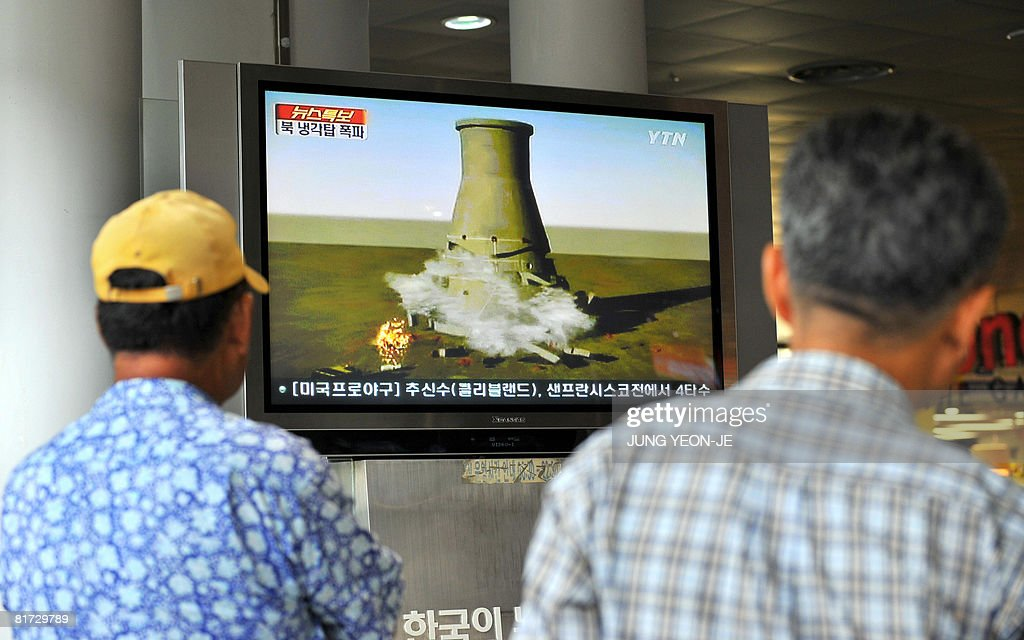 South Koreans watch a TV news programme at a railway station in Seoul on June 27 2008 that shows a video of a simulation of the planned blowup of a...