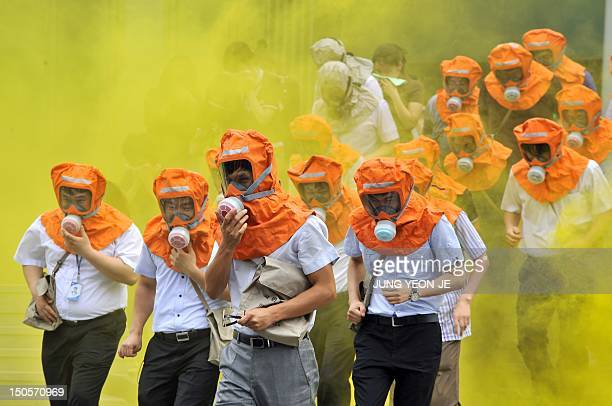 South Koreans wearing gas masks run out of a building during a civil defence drill in Seoul on August 22 2012 The drill comes amid high crossborder...