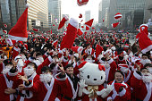 South Koreans wearing Santa Claus outfits attend an event to promote Christmas at a charity event on December 24 2015 in Seoul South Korea The event...