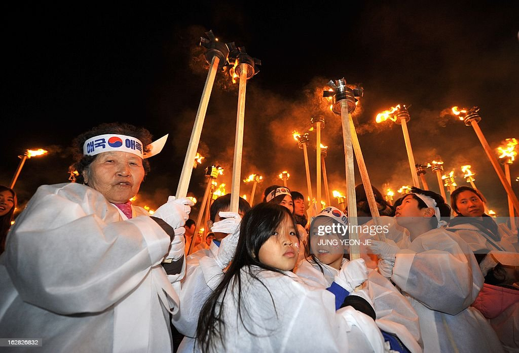 South Koreans wearing traditional costumes carry torches in their hands to celebrate the March 1 Independence Movement Anniversary in Cheonan, 90 kms south of Seoul, on February 28, 2013. South Koreans celebrate the public holiday of remembrance to mark the 1919 civilian uprising against Japanese colonial rule from 1910-1945.