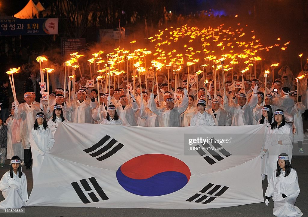 South Koreans wearing traditional costumes hold up burning toches with the national flag to celebrate the March 1 Independence Movement Anniversary in Cheonan, 90 kms south of Seoul, on February 28, 2013. South Koreans celebrate the public holiday of remembrance to mark the 1919 civilian uprising against Japanese colonial rule from 1910-1945.