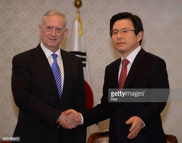 South Korea's acting President Hwang Kyoahn shakes hands with US Defense Secretary James Mattis prior their meeting at the Government Complex on...