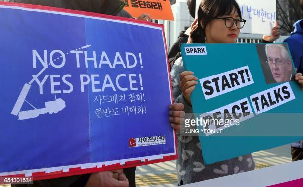 South Korea's antiwar activists hold placards showing a portrait of US Secretary of State Rex Tillerson during a rally against the planned deployment...