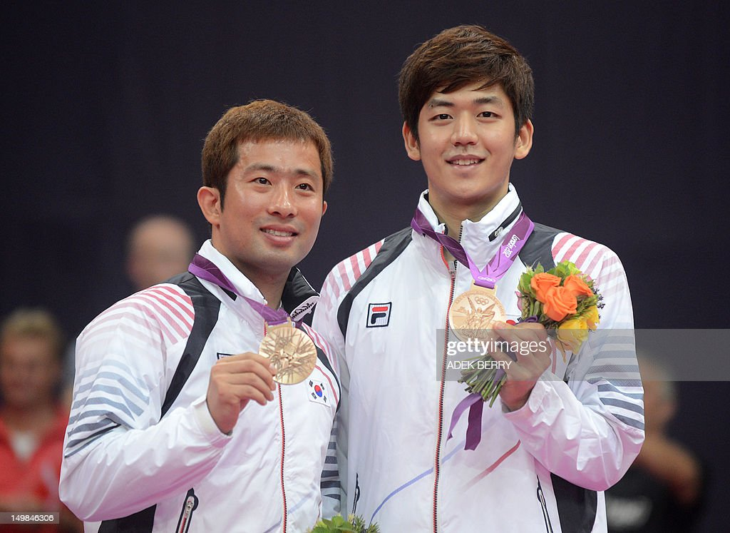 South Korea's Chung Jae Sung and Lee Yong Dae pose for pictures with their bronze medals after beating Malaysia's Koo Kien Keat and Tan Boon Heong in the Men's Doubles badminton bronze medal match at the London 2012 Olympic Games in London, on August 5, 2012.