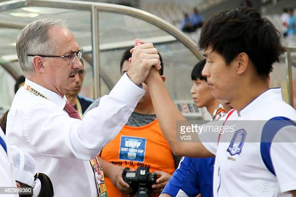 South Korea's coach Uli Stielike claps with team member in group match between Japan and South Korea during EAFF East Asian Cup 2015 at Wuhan Sports...