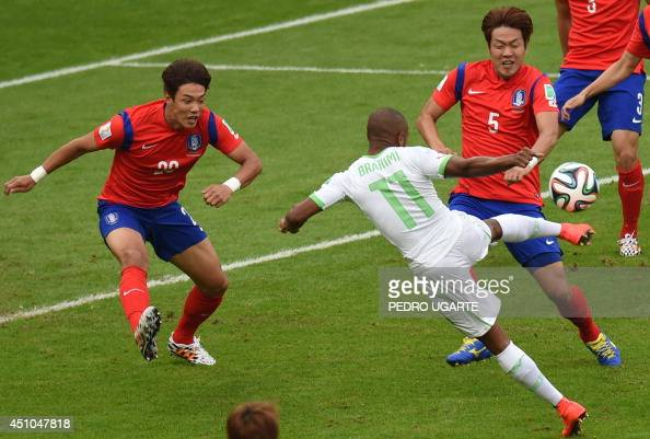 South Korea's defender Hong JeongHo and South Korea's defender Kim YoungGwon fight for the ball with Algeria's midfielder Yacine Brahimi during a...