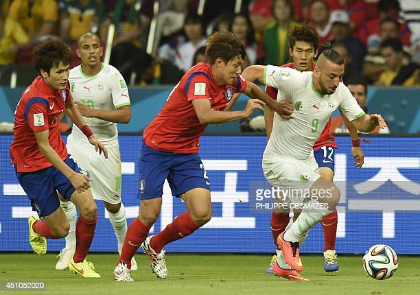 South Korea's defender Hong JeongHo fights for the ball with Algeria's forward Nabil Ghilas during a Group H football match between South Korea and...
