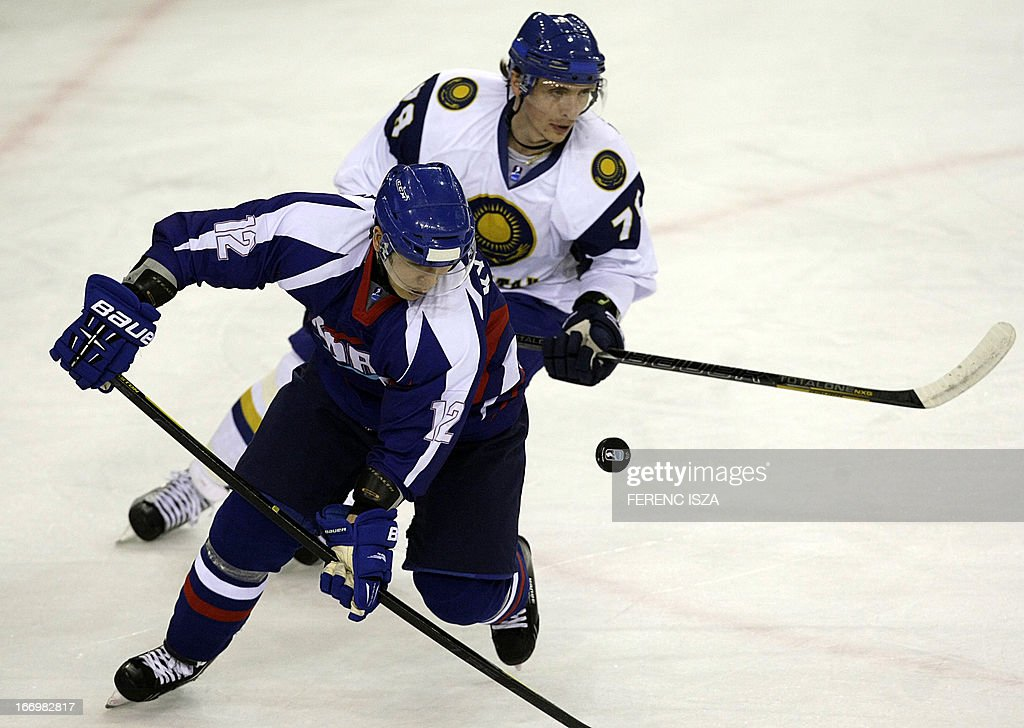 South Korea's defender Yoon Kyungwon (L) fights for the puck with Kazakhstan's forward Maxim Belyayev (R) on April 19, 2013 at the Budapest Sport Arena during their IIHF Ice Hockey World Championship Division 1 Group A match. ISZA