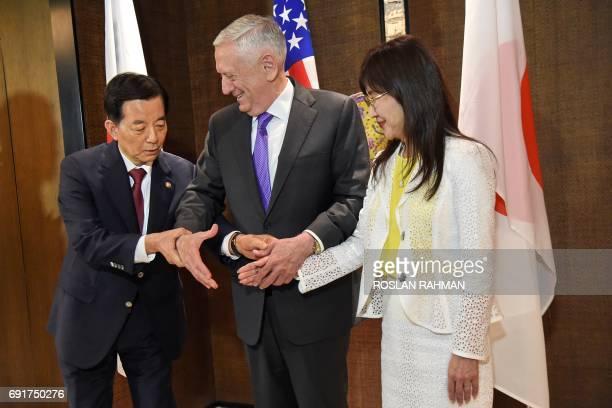 South Korea's Defense Minister Han MinKoo shows US Pentagon chief Jim Mattis how to pose for a trihandshake as Japan's Defence Minister Tomomi Inada...