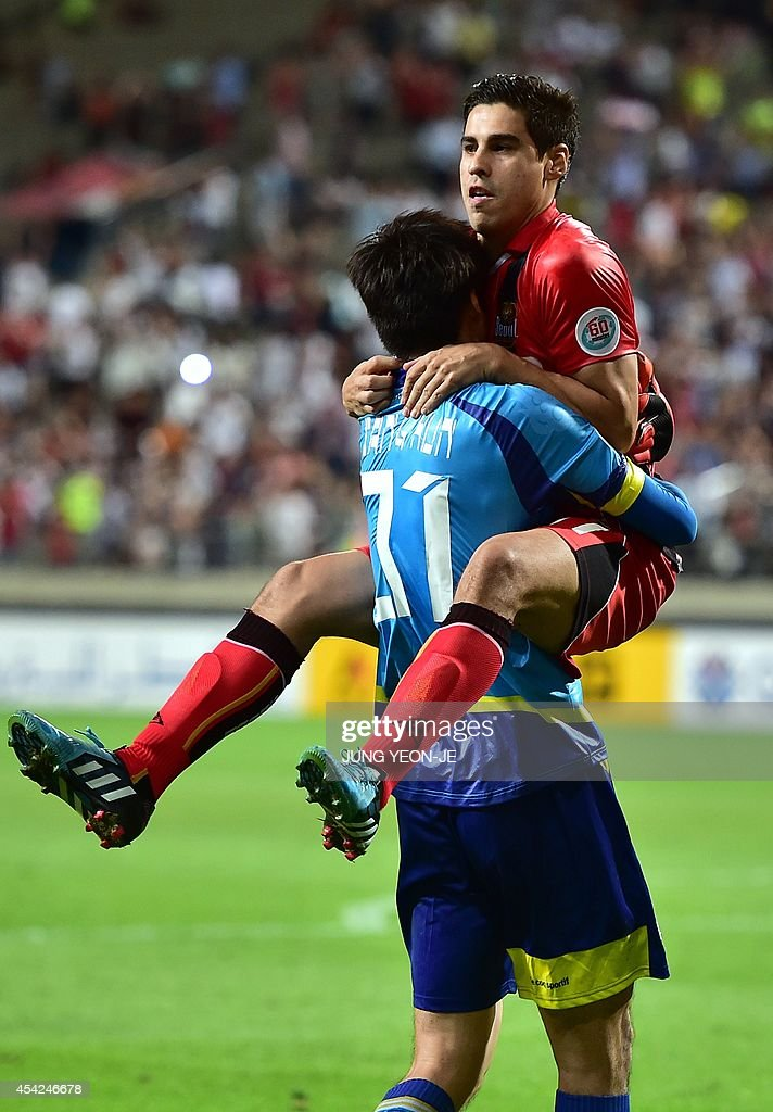 South Korea's FC Seoul goalkeeper Yu Sang-Hun (L) and midfielder Molina Uribe (R) celebrate their victory against South Korea's Pohang Steelers after the penalty shootout during the AFC Champions League quarter final football match in Seoul on August 27, 2014. FC Seoul beat Pohang Steelers 3-0 on spot kicks after a tie.