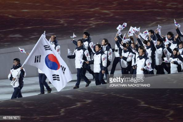 South Korea's flag bearer speed skater Lee KyouHyuk leads his national delegation during the opening ceremony of the 2014 Winter Olympics on February...