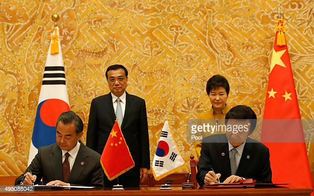 South Korea's Foreign Minister Yun ByungSe and China's Foreign Minister Wang Yi sign a document as South Korean President Park GeunHye and Chinese...